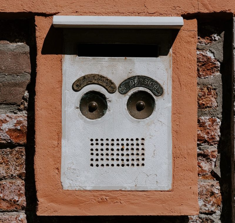 an electronic call box on a brick wall